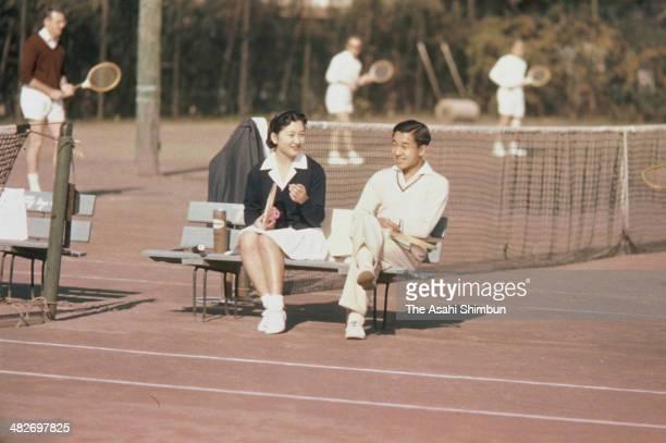 Crown Prince Akihito and Michiko Shoda talk while enjoying tennis at Tokyo Lawn Tennis Club on December 6, 1958 in Tokyo, Japan.