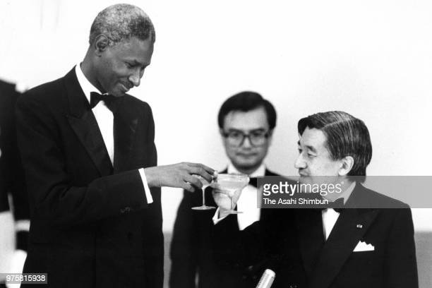 Crown Prince Akihito and Senegalese President Abdou Diouf toast glasses during the state dinner at the Imperial Palace on June 29 1988 in Tokyo Japan