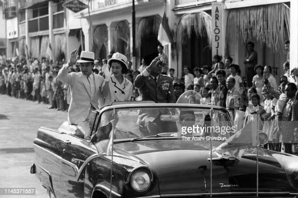 Crown Prince Akihito, Crown Princess Michiko and Indonesian President Sukarno wave to well-wishers on a car on February 3, 1962 in Denpasar,...