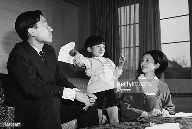 Crown Prince Akihito of Japan and Crown Princess Michiko with their son Prince Hiro, aka Crown Prince Naruhito of Japan, making paper aeroplanes on...