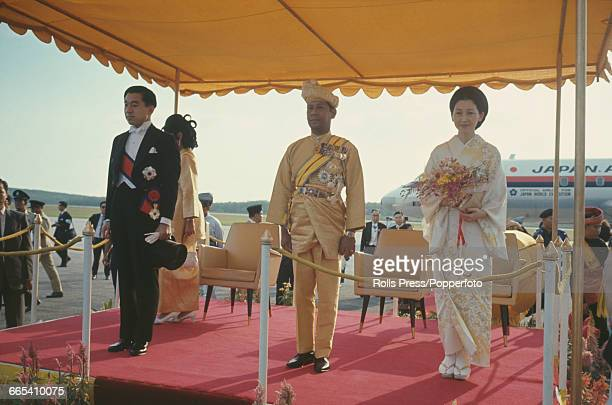 Crown Prince Akihito of Japan and his wife Michiko Shoda stand either side of Abdul Halim, Sultan of Kedah as they arrive at an airport in Kuala...