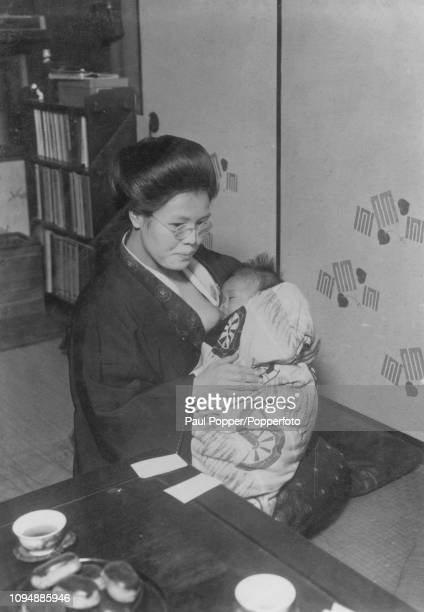 Crown Prince Akihito of Japan pictured being breast fed by nurse Sada Kitano in the nursery at the Imperial Palace in Tokyo Japan in 1934