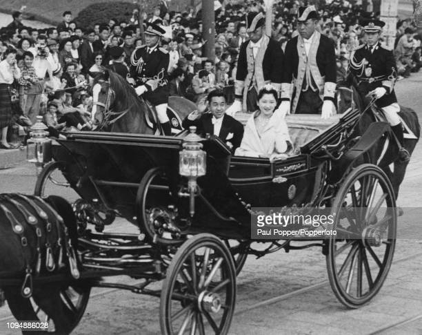 Crown Prince Akihito of Japan pictured on left with his wife Princess Michiko seated in a horse drawn carriage as they wave to cheering crowds of...