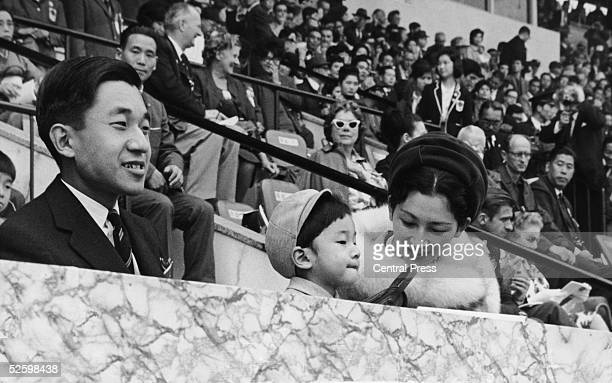 Crown Prince Akihito of Japan watches the start of the marathon at the 1964 Tokyo Olympics accompanied by his wife Michiko and their son Naruhito