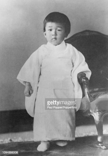 Crown Prince Akihito of Japan, who was born in 1933, pictured standing beside a chair in a palace in Japan circa 1935.