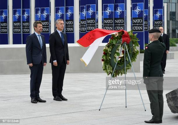 Crown Prince Frederik of Denmark and NATO Secretary General Jens Stoltenberg take part in a moment of silence during a wreath-laying ceremony at the...