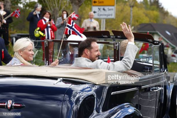 Crown Prince Haakon of Norway and Crown Princess MetteMarit of Norway wave out of a car during the May 17th celebration outside their home Skaugum in...