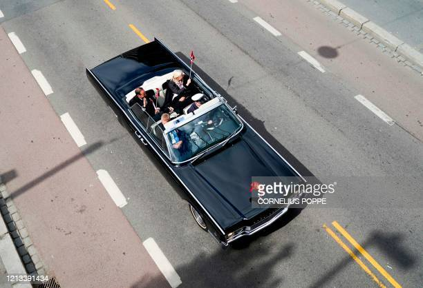 Crown Prince Haakon of Norway and Crown Princess MetteMarit of Norway sit in their old convertible car as they drive through the streets of Oslo...