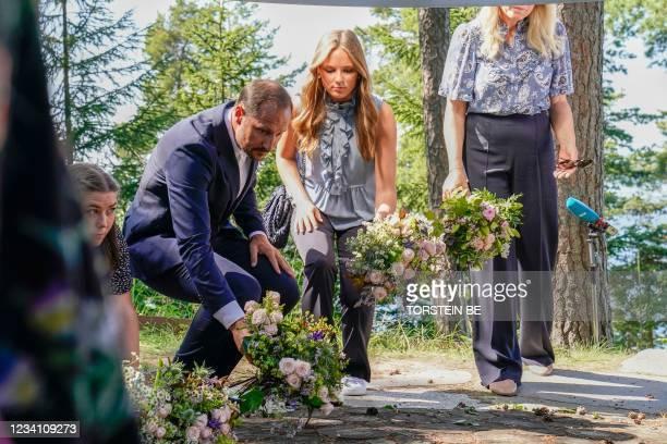 Crown Prince Haakon of Norway and Princess Ingrid Alexandra of Norway lay flowers during a memorial service on 22 July 2021, on Utoya, Norway, ten...