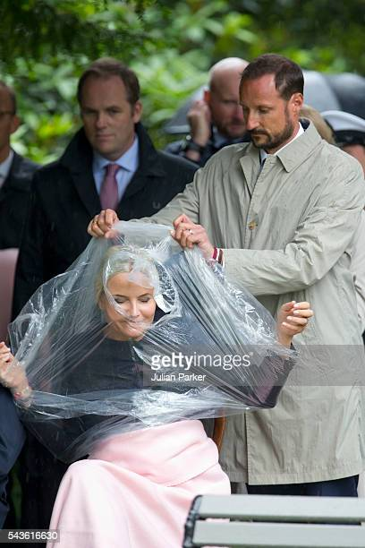 Crown Prince Haakon of Norway , assists his wife, Crown Princess Mette-Marit of Norway, putting on a rain poncho, on a visit to Kristiansand, during...