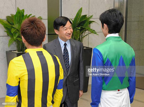 Crown Prince Naruhito is welcomed by jockeys Yutaka Take and Masayoshi Ebina as he attends the Japan Derby at Tokyo Racecourse on June 1 2014 in...