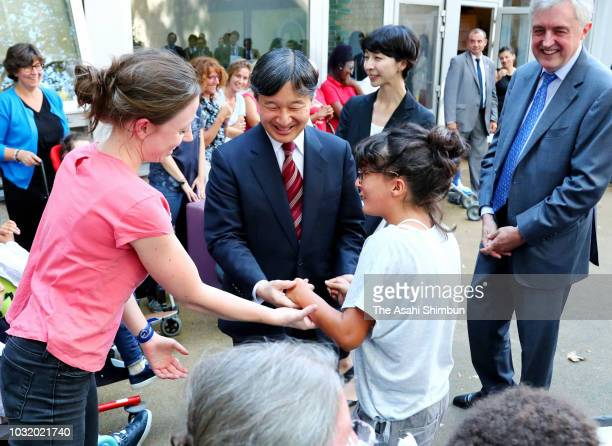 Crown Prince Naruhito of Japan dances with a girl during the visit to Les Amis de Karen facility for disabled people on September 11 2018 in Paris...