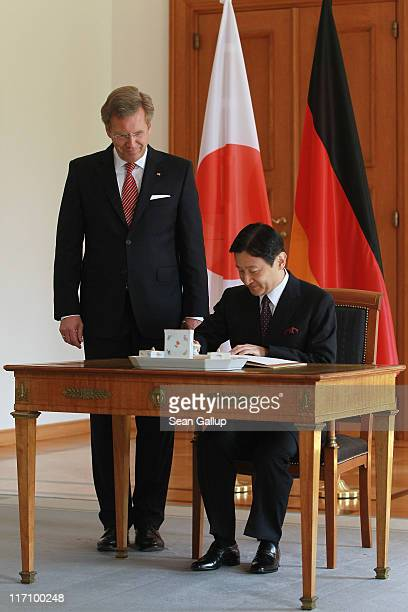H Crown Prince Naruhito of Japan signs the official guest book as German President Christian Wulff looks on at Bellevue Palace on June 22 2011 in...