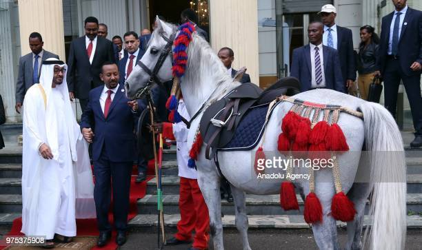 Crown Prince of Abu Dhabi Mohammed bin Zayed Al Nahyan receives a gift from Ethiopian Prime Minister Abiy Ahmed after their meeting at National...