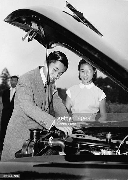 Crown Prince of Japan Akihito examining the engine of his 1954 Prince Motor Company car as his younger sister Princess Takako looks on circa 1955...