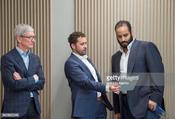 Crown Prince of Saudi Arabia Mohammed bin Salman Al Saud is being informed by a company official as he is flanked by CEO of Apple Tim Cook during his...