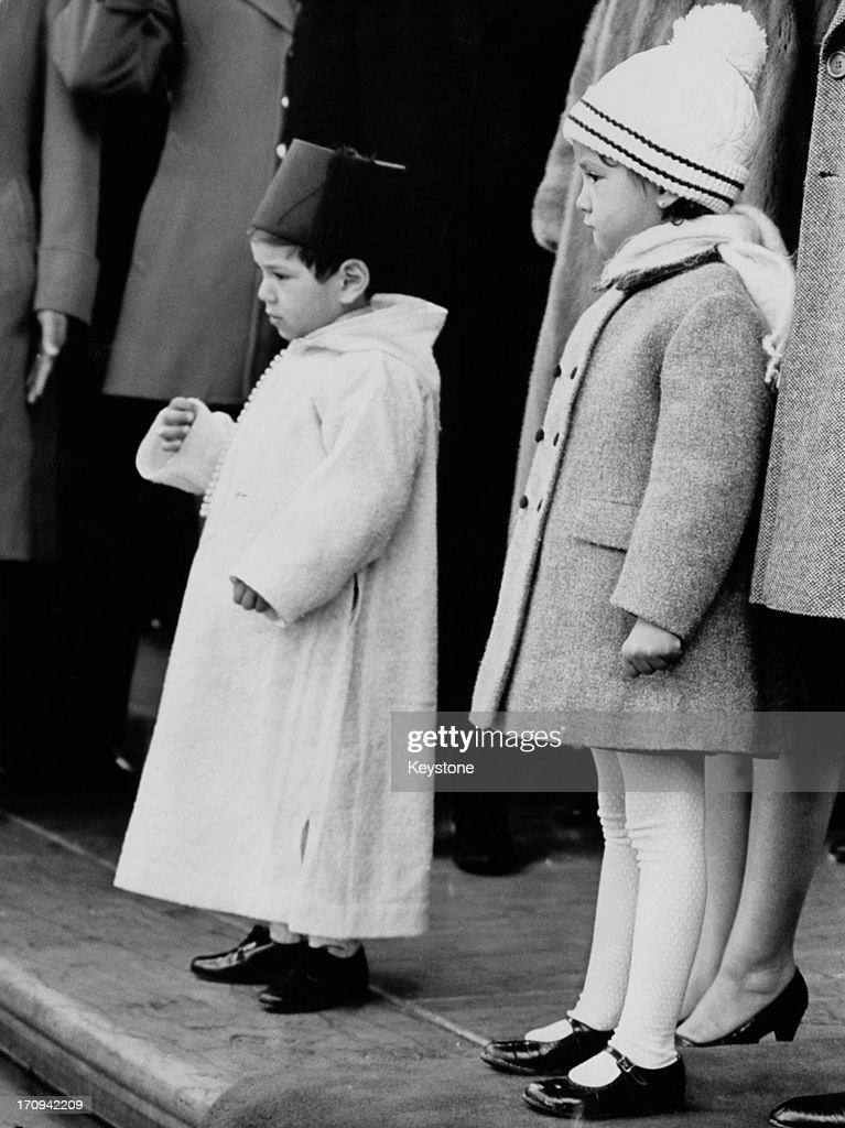 Crown Prince Sidi Mohammed (later Mohammed VI of Morocco, left) and his sister Princess Lalla Meryem on the north portico of the White House as their father, King Hassan II of Morocco is welcomed by US President Lyndon B. Johnson before official talks in Washington DC, 11th February 1967.