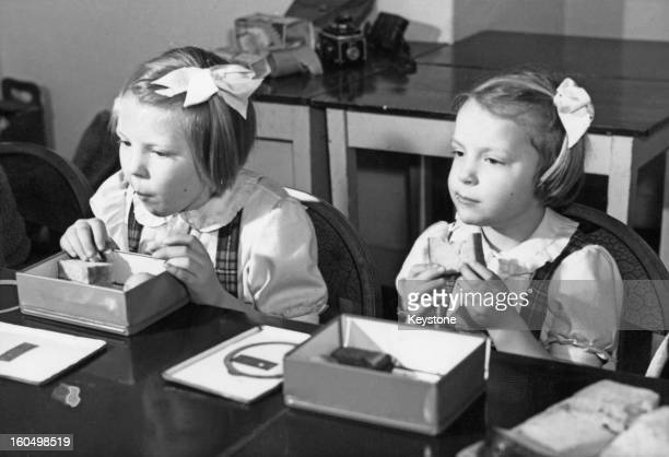 Crown Princess Beatrix of the Netherlands and her sister Princess Irene eating their lunch at primary school 'De Werkplaats', March 1946.