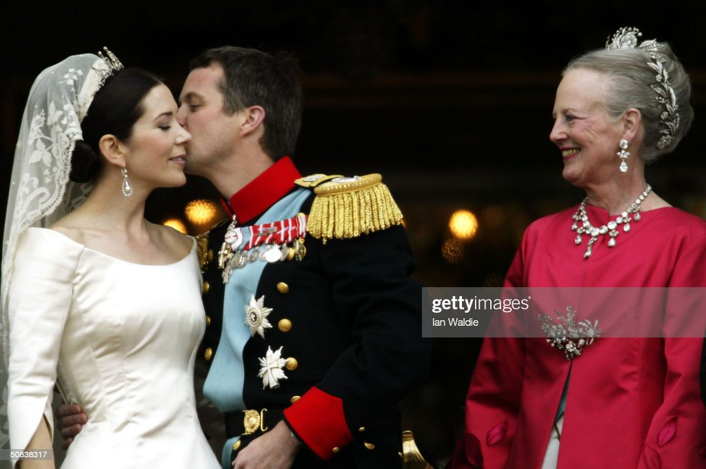 Crown Princess Mary and Crown Prince Frederik kiss as Queen Margrethe II of Denmark looks on as the Royal couple appear on the balcony of Christian VII's Palace after their wedding on May 14, 2004 in Copenhagen, Denmark. The romance began in 2000 when Miss Mary Elizabeth Donaldson met the heir to one of Europe's oldest monarchies over drinks at the Sydney Olympics, where he was with the Danish sailing team.