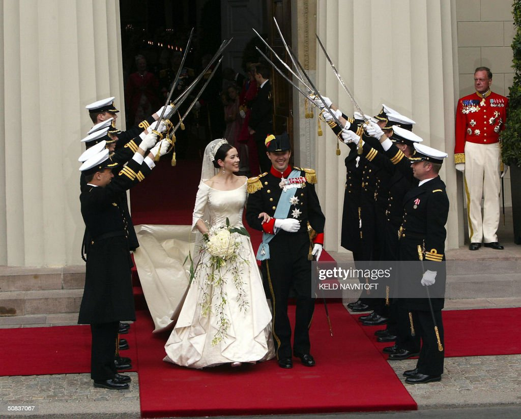Crown Princess Mary and Crown Prince Frederik of Denmark walk outside the Copenhagen Cathedral after their wedding as marine officers salute with their swards, 14 May 14 2004. AFP PHOTO/Keld Navntoft / SCANPX