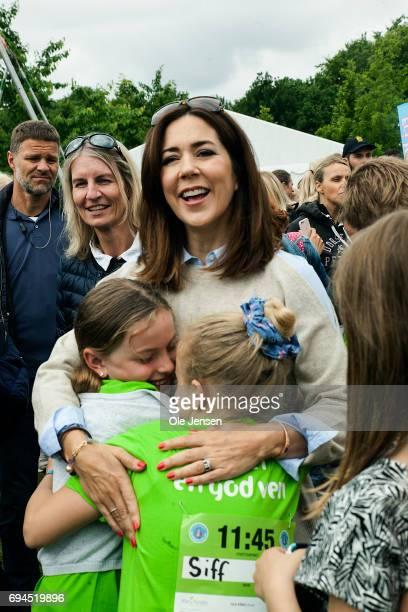Crown Princess Mary of Denmark is warmly welcomed by kids during the 'Children's Relay Run' in Faelledparken on June 10 2017 in Copenhagen Denmark...