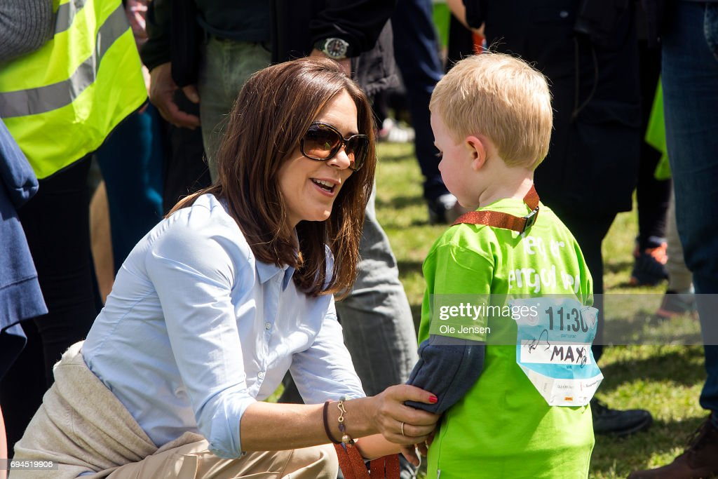 Crown Princess Mary of Denmark presents medal to a young runner having passed the finishing line at the 'Children's Relay Run' in Faelledparken on June 10, 2017 in Copenhagen, Denmark. The kids (age 0 - 8 years) relay run is part of the Crown Princess' organization 'The Mary Foundation's fight against bullying among children through building up safe community and interaction among them. The organisation ''Save the Children Denmark' (Red Barnet) was co-organizer of the event and the toy manufacturer LEGO, co-founder of the Mary Foundation, took also part in the event.