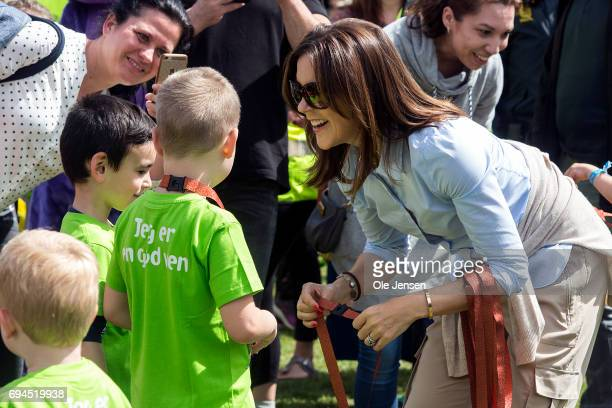 Crown Princess Mary of Denmark presents medal to a young runner having passed the finishing line at the 'Children's Relay Run' in Faelledparken on...