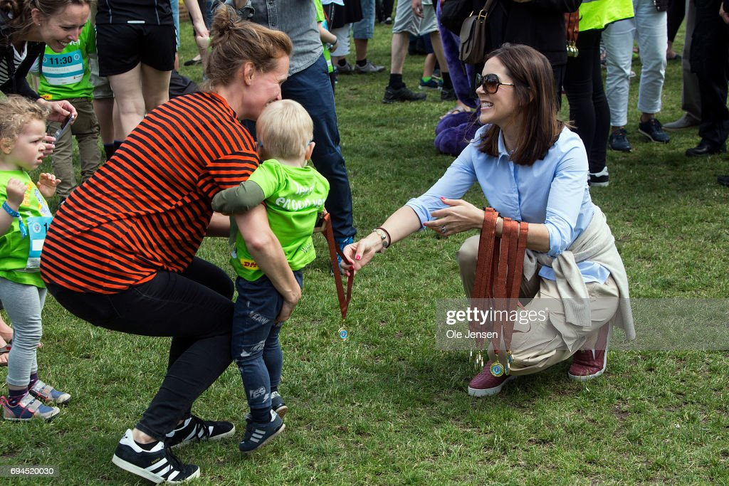 Crown Princess Mary of Denmark (R) presents medal to a young runner having passed the finishing line at the 'Children's Relay Run' in Faelledparken on June 10, 2017 in Copenhagen, Denmark. The kids (age 0 - 8 years) relay run is part of the Crown Princess' organization 'The Mary Foundation's fight against bullying among children through building up safe community and interaction among them. The organisation ''Save the Children Denmark' (Red Barnet) was co-organizer of the event and the toy manufacturer LEGO, co-founder of the Mary Foundation, took also part in the event.