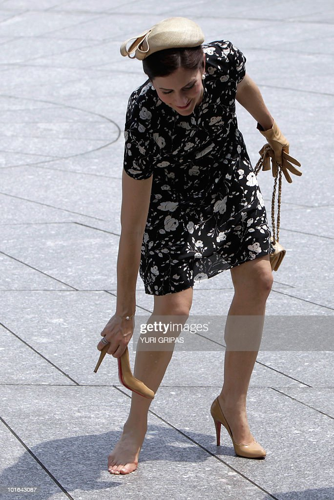 Crown Princess Mary of Denmark reaches for shoe as she and Crown Prince Frederik of Denmark are given a tour at Arlington National Cemetery in Arlington, Virginia on June 5, 2010.