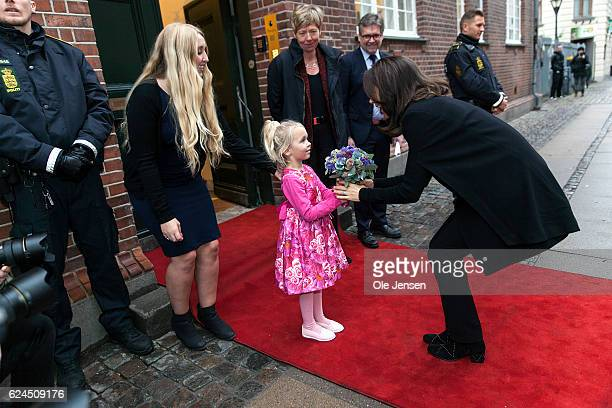 Crown Princess Mary of Denmark receives a bouquet from Meladie Mary Modler aged 5 during her visit to the Danish Mother's Aid's new family council...