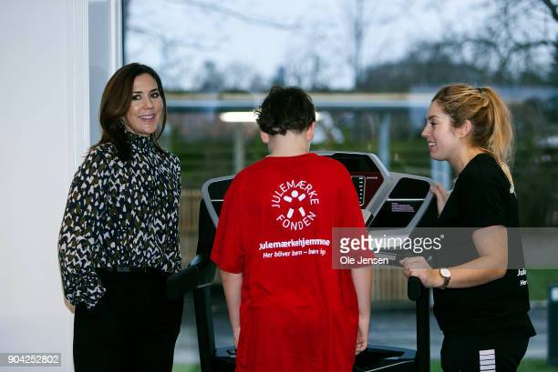Crown Princess Mary of Denmark speaks to a young boy doing physical exercise during the Christmas Seal Foundation home opening on January 12 2018 in...