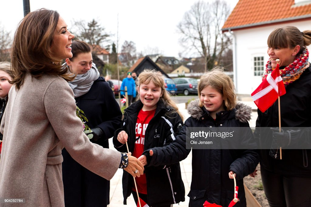 Crown Princess Mary of Denmark (C) speaks to kids with the Danish flag at her arrival to the Christmas Seal Foundation home opening on January 12, 2018 in Roskilde, Denmark. The Crown Princess is the patron of the Christmas Seal Foundation where labels are placed on mail during the festive period to help raise money for underprivileged children, through the sale of the annual Christmas Seal. Children suffering from psychological issues are then able to stay in one of the six homes in Denmark, for a period of up to 10 weeks to help them rehabilitate.