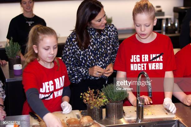 Crown Princess Mary of Denmark speaks to young kids preparing food during her visits to the Christmas Seal Foundation home opening on January 12 2018...