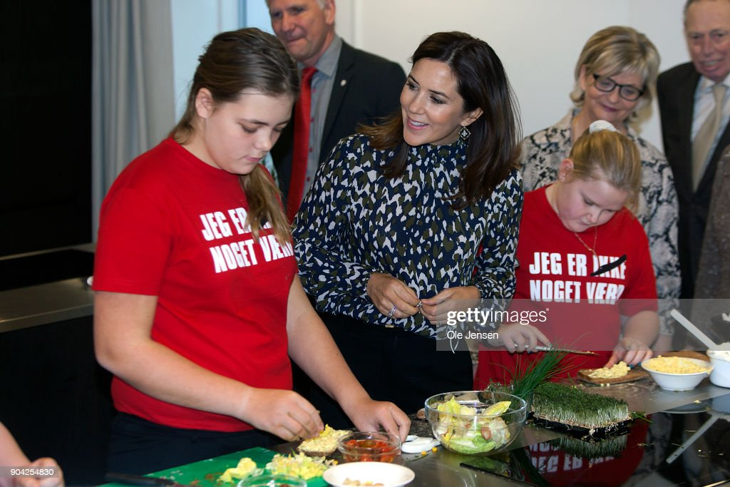 Crown Princess Mary of Denmark (C) speaks to young kids preparing food during her visits to the Christmas Seal Foundation home opening on January 12, 2018 in Roskilde, Denmark. The Crown Princess is the patron of the Christmas Seal Foundation where labels are placed on mail during the festive period to help raise money for underprivileged children, through the sale of the annual Christmas Seal. Children suffering from psychological issues are then able to stay in one of the six homes in Denmark, for a period of up to 10 weeks to help them rehabilitate. The text on the childrens T-shirts reads: : 'I am worth nothing' - but with a cross over *nothing''.