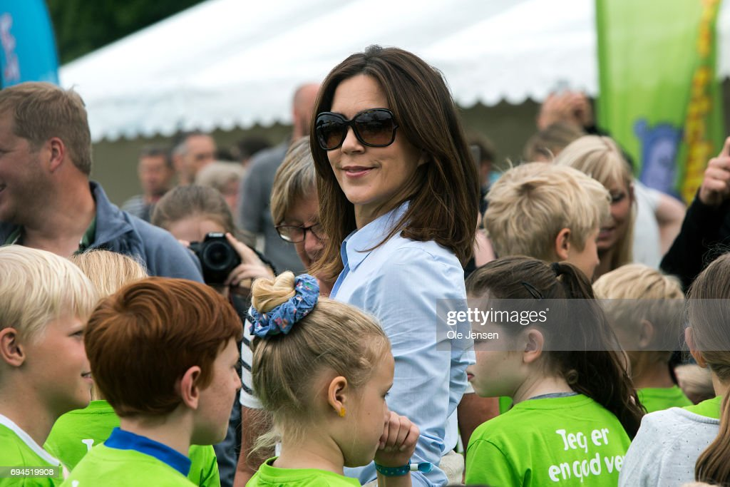 Crown Princess Mary of Denmark (C) surrounded by kids during the warm-up exercise at the 'Children's Relay Run' in Faelledparken on June 10, 2017 in Copenhagen, Denmark. The kids (age 0 - 8 years) relay run is part of the Crown Princess' organization 'The Mary Foundation's fight against bullying among children through building up safe community and interaction among them. The organisation ''Save the Children Denmark' (Red Barnet) was co-organizer of the event and the toy manufacturer LEGO, co-founder of the Mary Foundation, took also part in the event.