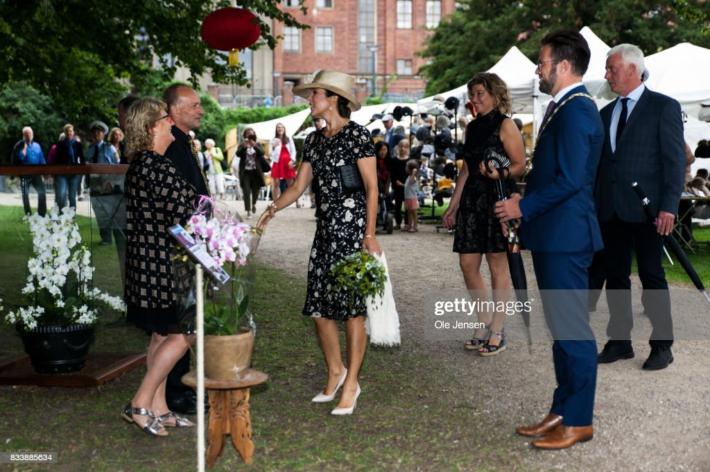 Crown Princess Mary (R) speaks to an exhibitor at Odense Flower Festival which she is to open officially and where she is to be presented to a new developed rose on August 17, 2017 in Odense, Denmark. The exhibitor, Nursery Ellelund, produces yearly one million orchids. The festival opens today and ends August 20 and takes place all over the inner city with some 100.000 plants made up with the theme 'What a Woinderful World' and urban gardening.