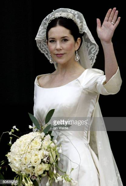 Crown Princess Mary waves to the crowd as the she and Crown Prince Frederik of Denmark arrive at Christian VII's Palace after their wedding on May 14...