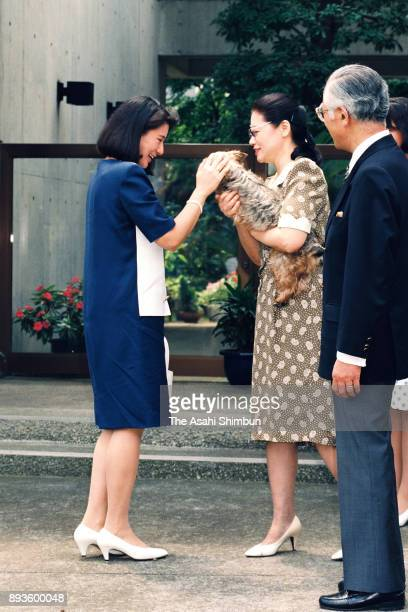 Crown Princess Masako kisses the family pet dog Chocola while Hisashi Owada and Yumiko Owada watches on arrival at her parents home for the first...