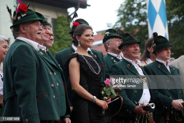 Crown Princess Victoria of Sweden and her husband Prince Daniel Duke of Vastergotland pose with Bavarian dressed riflemen in front of Brauereigasthof...