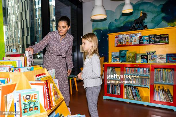 Crown Princess Victoria of Sweden and Maija Sinisalo look at childrens books during an inauguration ceremony for a sculpture of Swedish childrens...