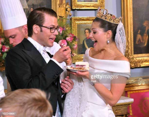 Crown Princess Victoria of Sweden and Prince Daniel, Duke of Vastergotland share a slice of wedding cake during the Wedding Banquet at the Royal...