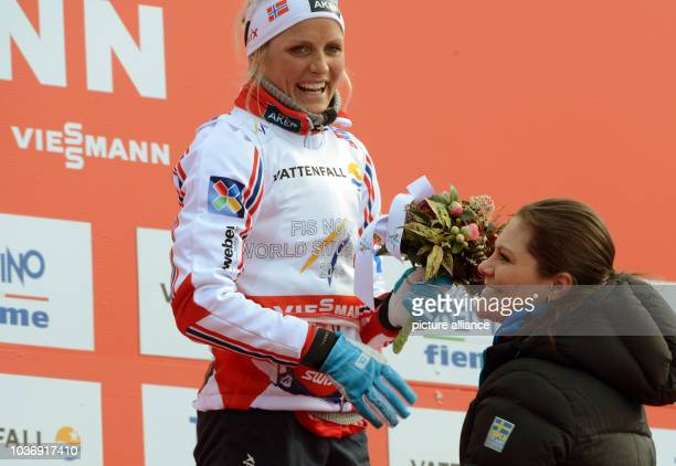 Crown Princess Victoria of Sweden congratulates winner Therese Johaug of Norway during the flower ceremony after the Women's 10 km Free Individual...