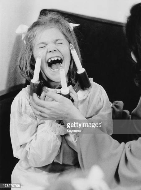 Crown Princess Victoria of Sweden laughs as her mother Queen Silvia of Sweden dresses her in a costume 1984