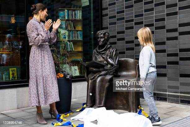Crown Princess Victoria of Sweden participates in a ribbon cutting ceremony with child Maija Sinisalo during an inauguration ceremony for a sculpture...