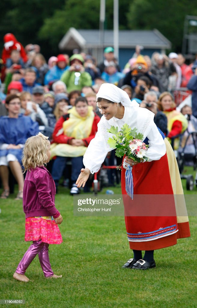 Crown Princess Victoria of Sweden receives flowers from a young girl as she attends an event celebrating her 34th birthday at Borgholm's Idrottsplats on July 14, 2011 in Borgholm, Sweden.