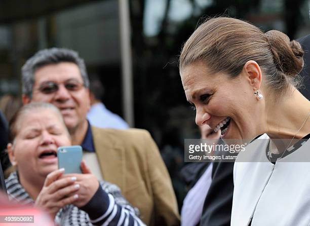 Crown Princess Victoria of Sweden smiles as she is being pictured by a woman while leaving the Gold Museum after visiting it on October 23, 2015 in...