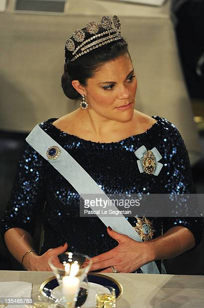 Crown Princess Victoria of Sweden touches her pregnant belly at the Nobel Prize Banquet at Stockholm City Hall on December 10 2011 in Stockholm Sweden