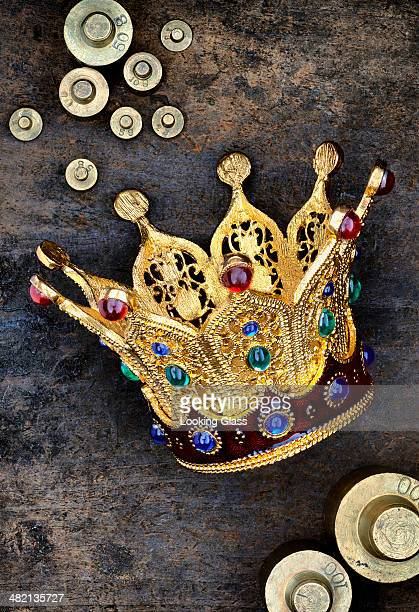Crown, weights and coins on stone surface