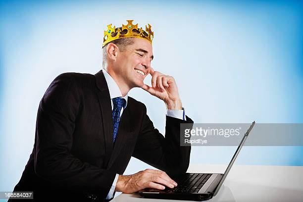 crowned businessman smiles down at his laptop - king royal person stock pictures, royalty-free photos & images