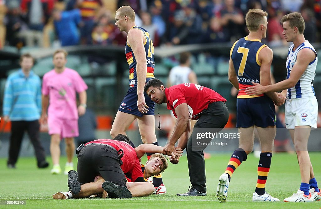A Crows fan is caught by security guards after their win during the round one AFL match between the Adelaide Crows and the North Melbourne Kangaroos at Adelaide Oval on April 5, 2015 in Adelaide, Australia.